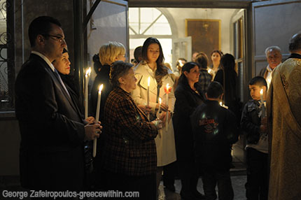 Greek families with candles in their hands.