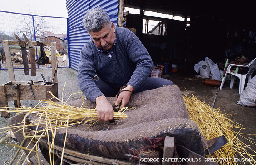 The last saddler of Litochoron fills a saddle with rye straw.