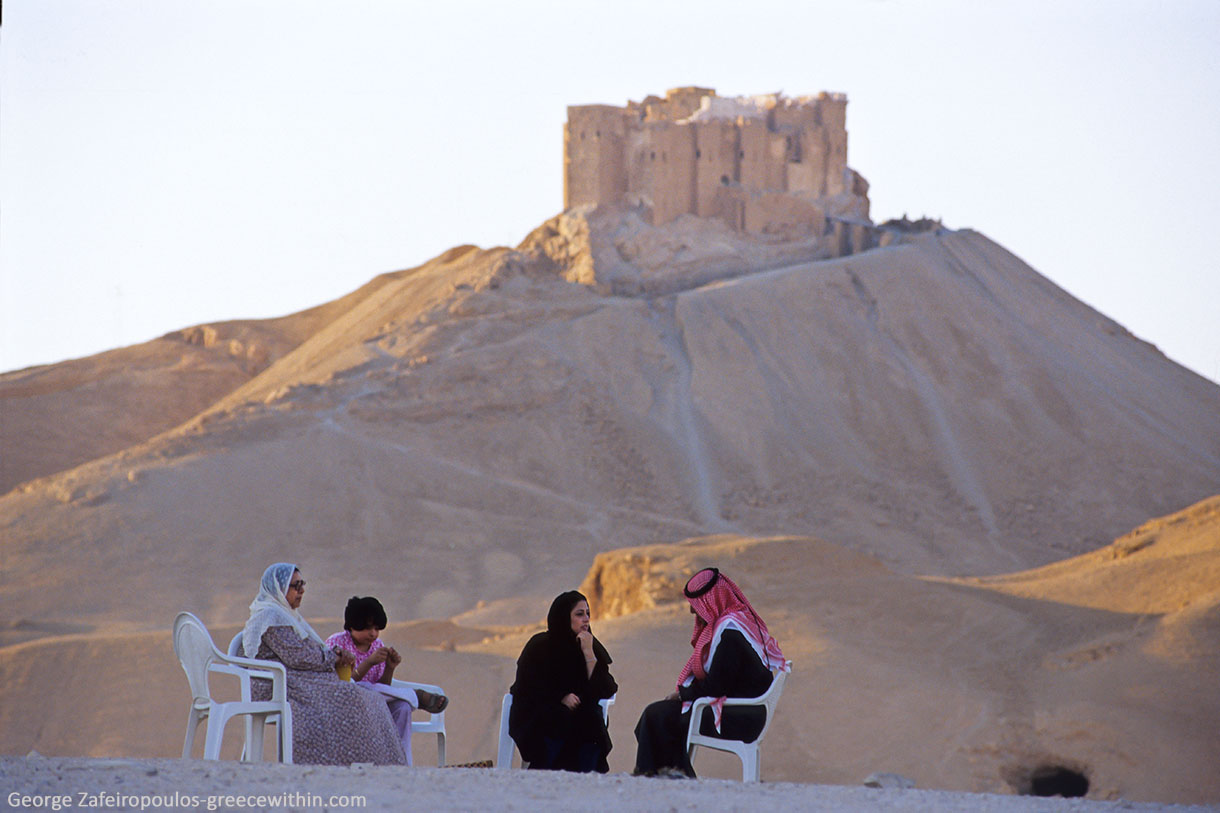 A family is getting some rest under the Arabic castle Qala'at ibn Maan's shadow, next to Tadmor oasis, in Palmyra of Syria. The temperature is 47 degrees under the shade and there's deathly silence.